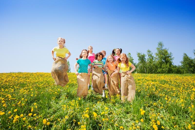 Enfants drôles sautant dans des sacs jouant ensemble image libre de droits