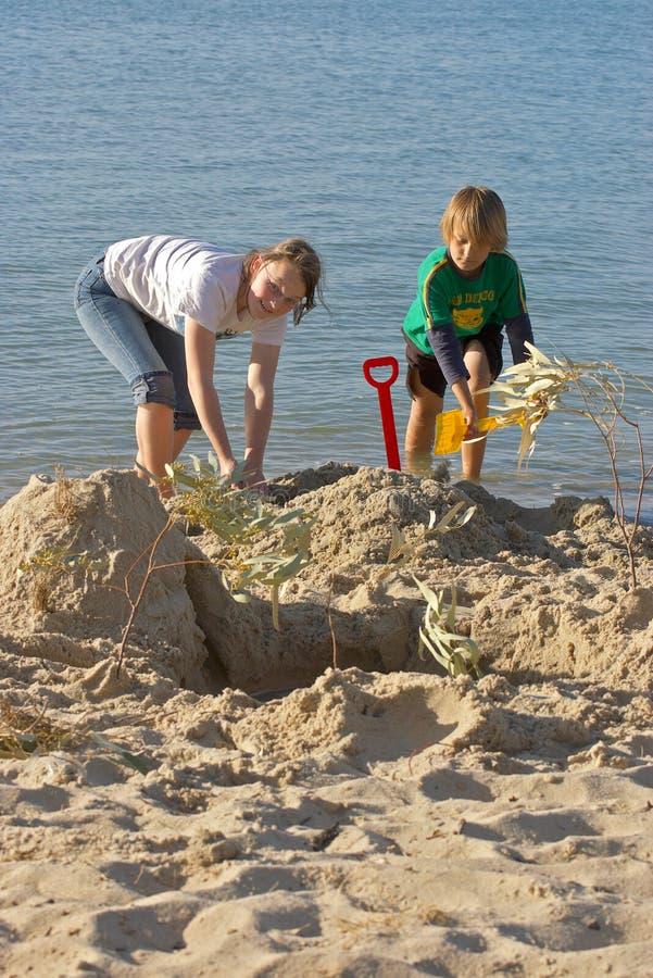 enfants effectuant des châteaux de sable photos stock