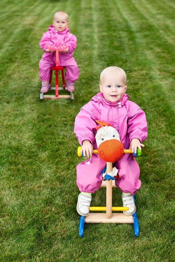 Enfants en bas âge sur des chevaux d'oscillation image libre de droits