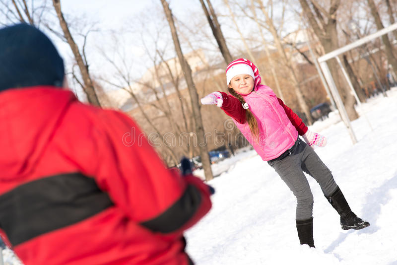 Enfants en parc d'hiver jouant des boules de neige images libres de droits