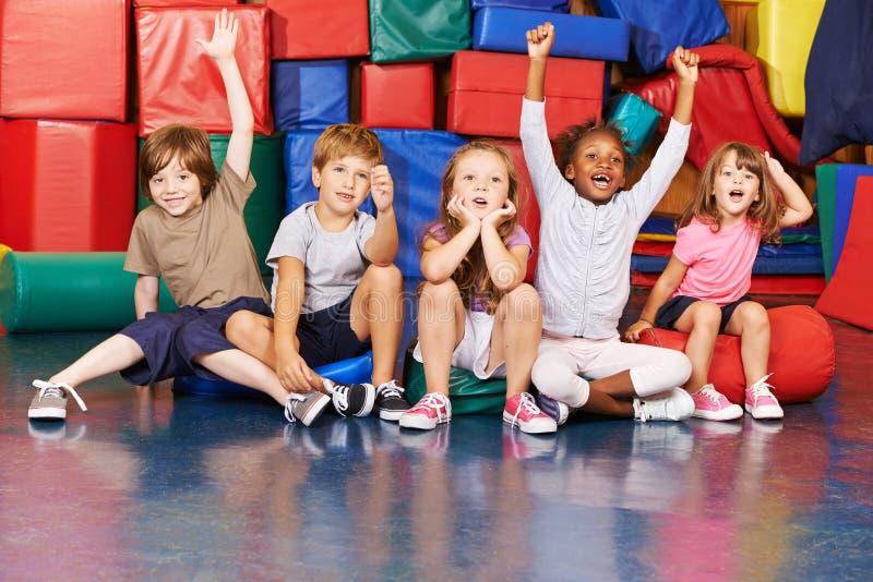 Enfants encourageant dans le gymnase de l'école photos stock