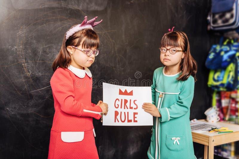 Enfants ensoleillés mignons se tenant près du tableau noir avec la règle de filles de signe images stock