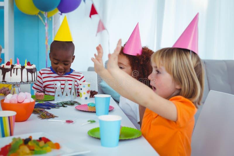Enfants enthousiastes appréciant une fête d'anniversaire images stock