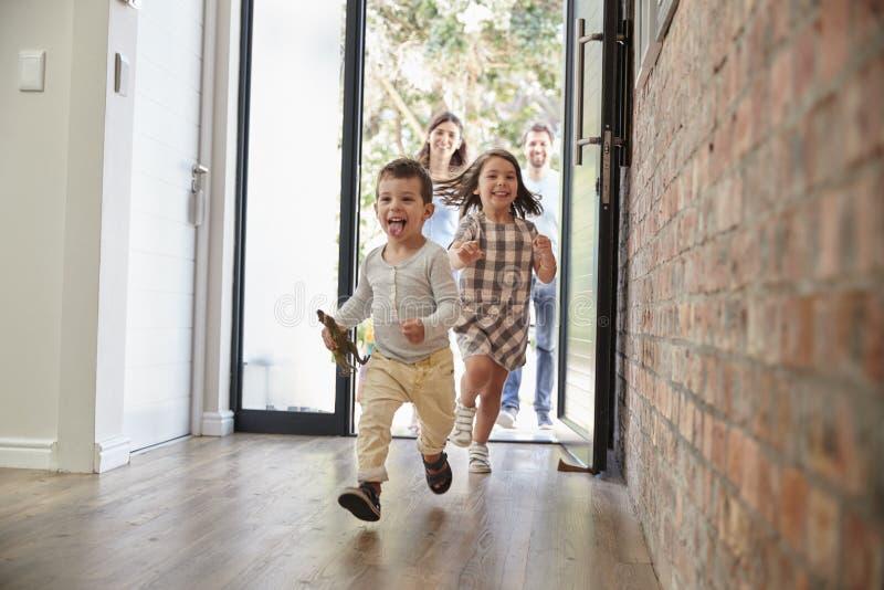 Enfants enthousiastes arrivant à la maison avec des parents photographie stock libre de droits