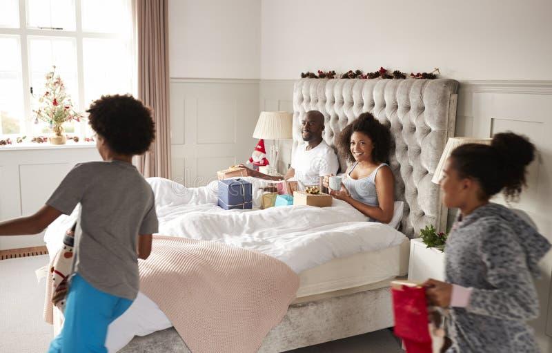 Enfants enthousiastes courant dans leur chambre à coucher de ½ de ¿ de parentsï le matin de Noël, parents s'asseyant dans le lit photo libre de droits