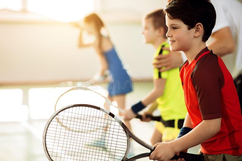 Enfants enthousiastes jouant le tennis sur la cour image stock