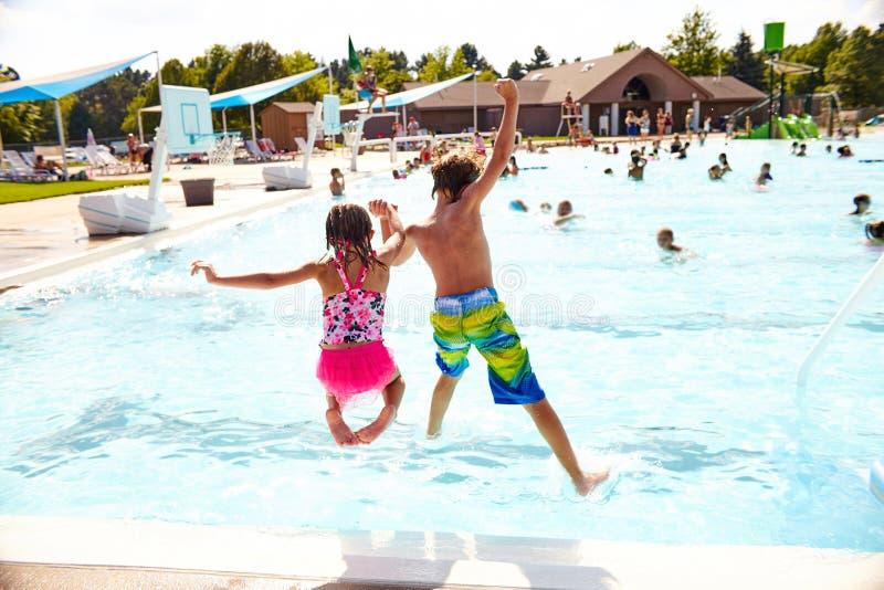 Enfants enthousiastes sautant dans la piscine tenant des mains images libres de droits