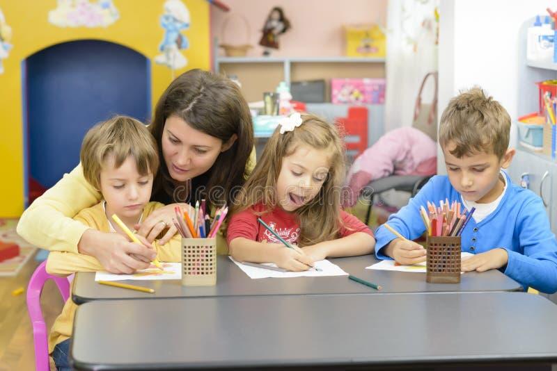 Enfants et éducateur Playing au jardin d'enfants photographie stock