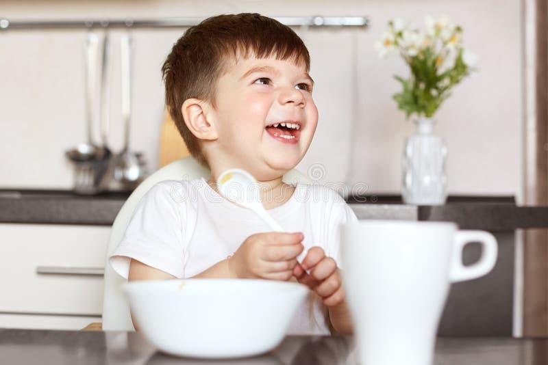 Enfants et concept de nutrition Le petit enfant mignon avec plaisir de sourire mange des céréales savoureuses et boit du thé, éta photos stock