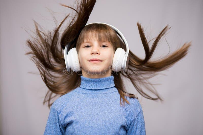 Enfants et concept de technologie - fille de sourire avec des écouteurs écoutant la musique d'isolement sur le blanc Long vol de  images libres de droits