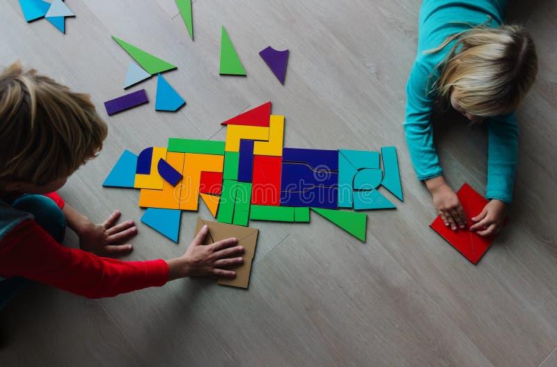 Enfants et fillettes jouant avec le puzzle, faisant du tangram photographie stock
