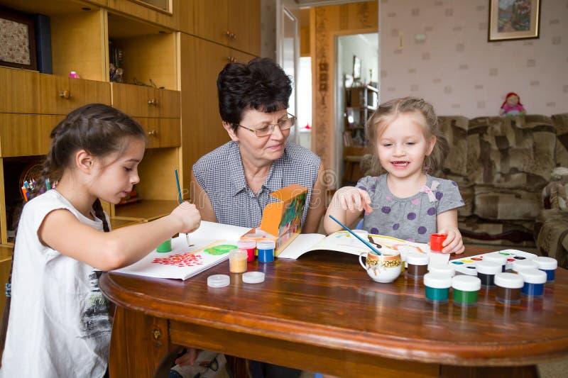 Enfants et grand-mère peignant à la maison image stock