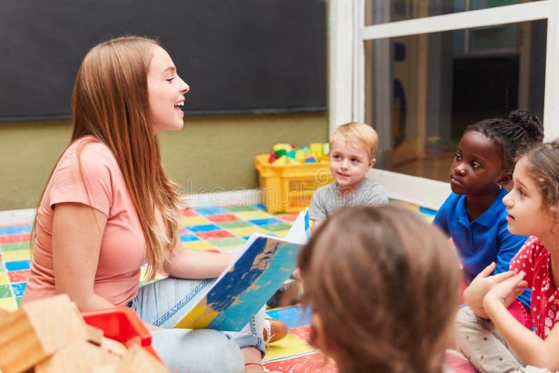 Enfants et institutrice gardienne lisant à haute voix image libre de droits