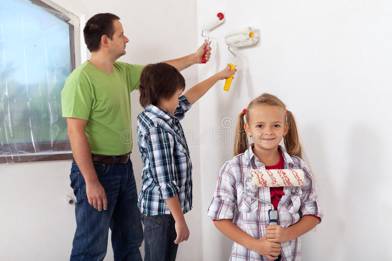 Enfants et leur père peignant une salle image stock