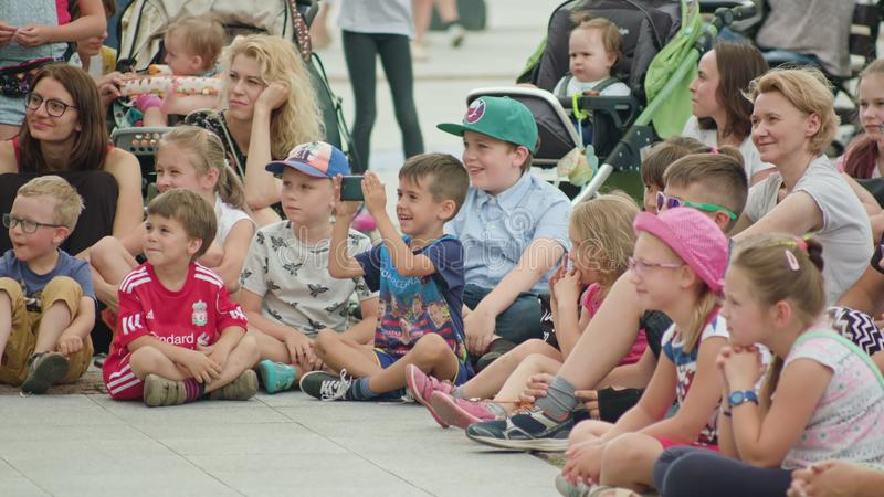 Enfants et mères observant la représentation de rue images libres de droits