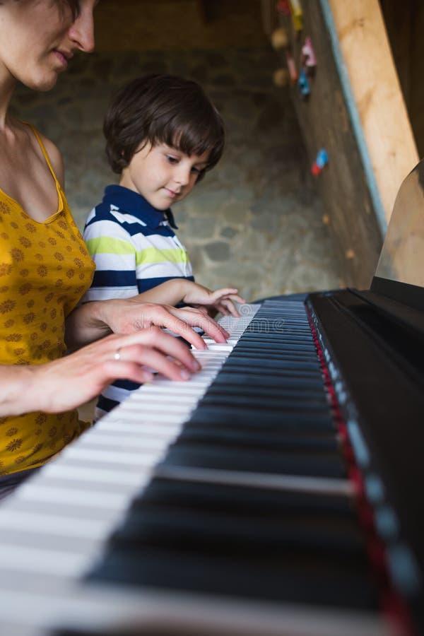 Enfants et mains des femmes sur les clés de piano photographie stock libre de droits