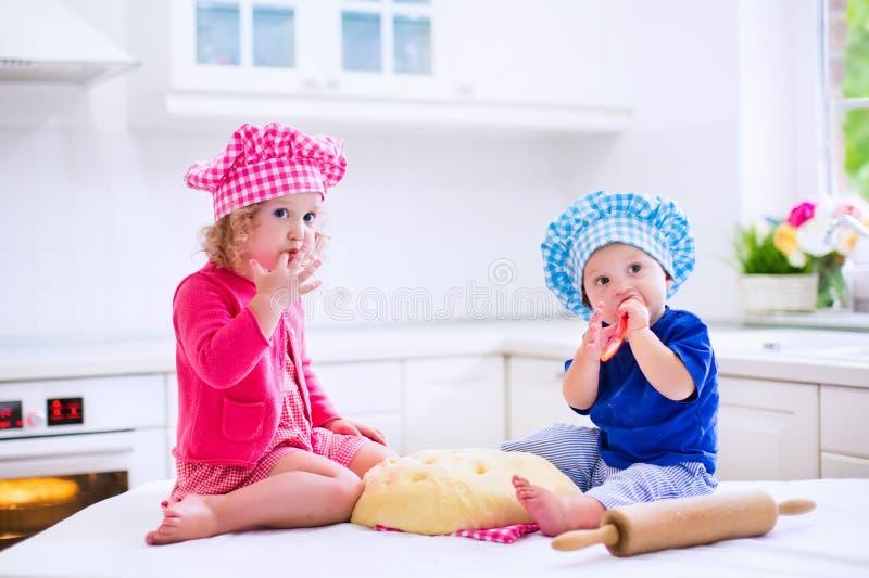 Enfants faisant cuire au four dans une cuisine blanche photographie stock