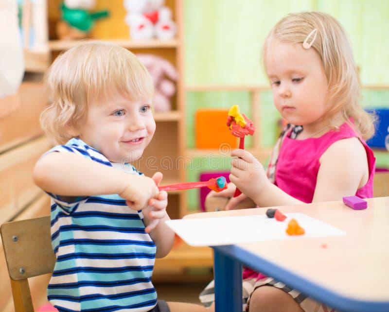 Enfants faisant des arts et des métiers dans le jardin d'enfants avec l'intérêt photo libre de droits