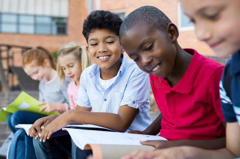 Enfants faisant des devoirs extérieurs photographie stock libre de droits