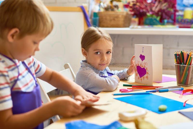Enfants faisant la carte cadeaux dans la leçon d'art et de métier image stock