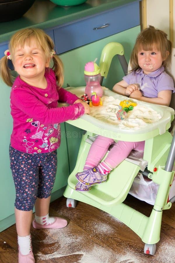 Enfants faisant le désordre dans une cuisine photo stock