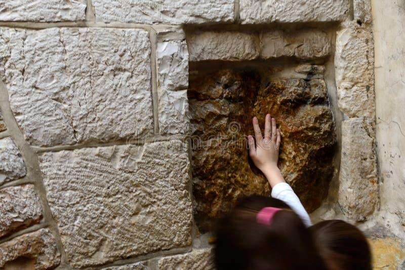 Enfants faisant le souhait et touchant la pierre sainte avec espoir photos stock
