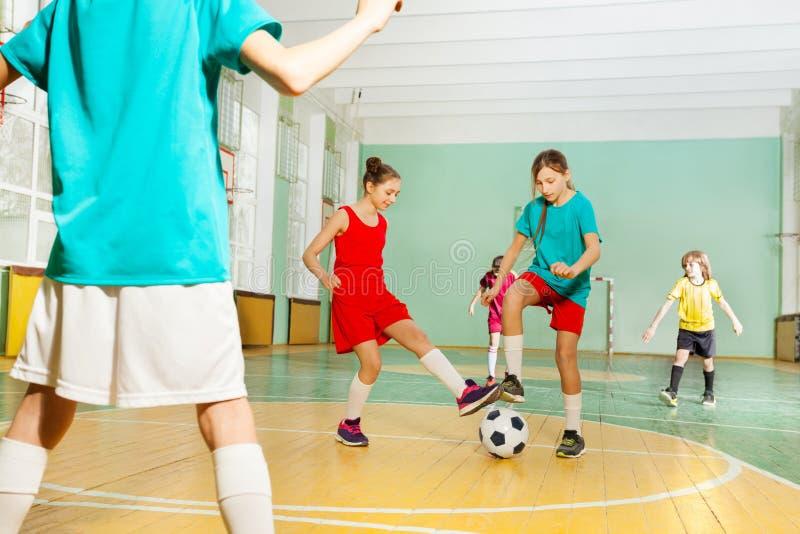 Enfants formant le football dans la salle de gymnastique d'école images libres de droits