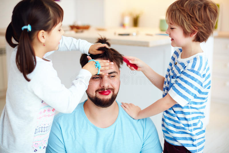 Enfants fous faisant la coiffure et le maquillage fous au papa à la maison photos stock