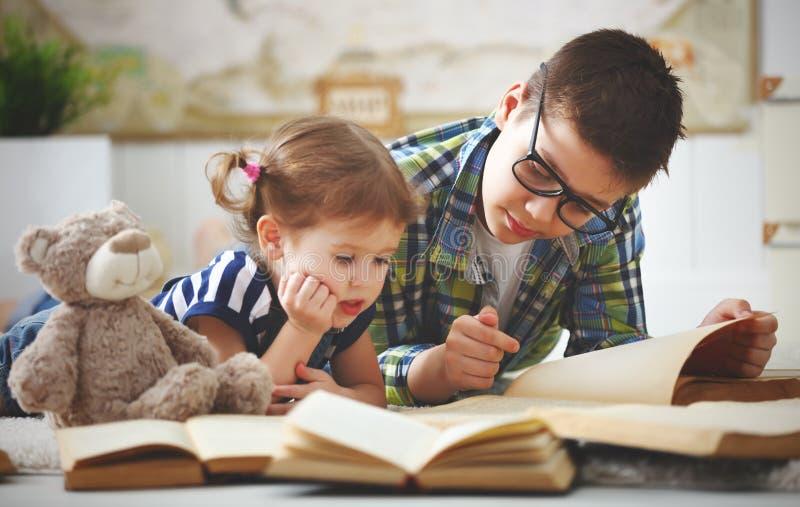 Enfants frère et soeur, garçon et fille lisant un livre photographie stock