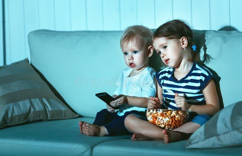 Enfants frère et soeur regardant la TV dans la soirée images libres de droits