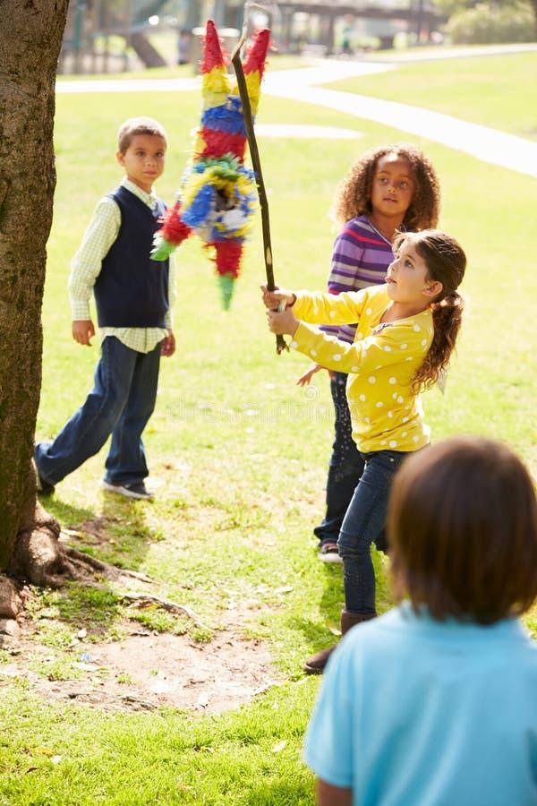 Enfants frappant le Pinata à la fête d'anniversaire image stock