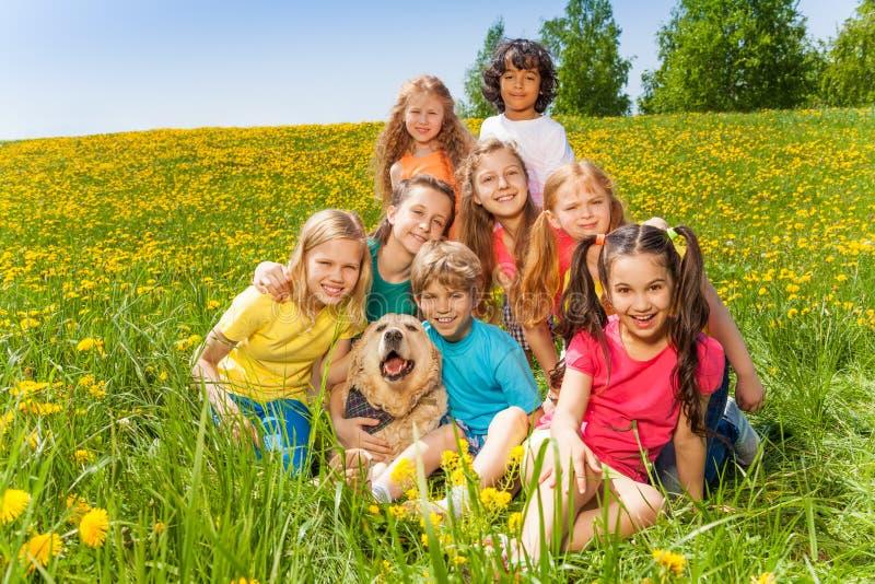 Enfants gais avec le chien se reposant sur l'herbe image stock