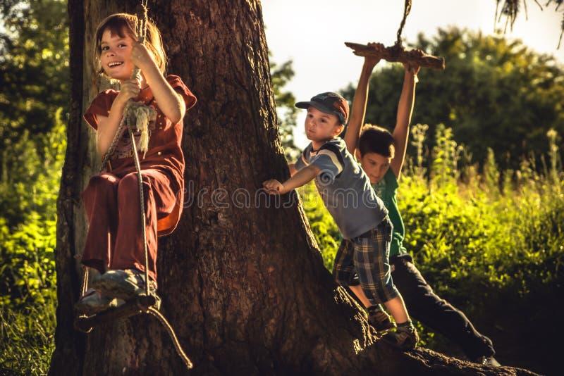 Enfants gais ayant l'amusement dehors dans la forêt pendant des vacances d'été dans la campagne symbolisant l'enfance insouciant  image stock