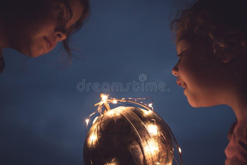 Enfants gais curieux regardant le globe brillant de la terre dans la curiosité de concept de ciel nocturne photographie stock libre de droits