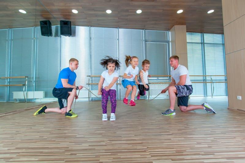 Enfants gais de sourire dans l'âge scolaire jouant ainsi que la corde à sauter dans le gymnase Enfants à la leçon d'éducation phy image stock