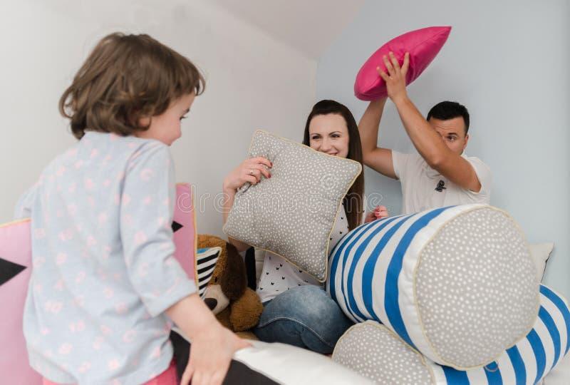 Enfants gais et parents ayant le combat d'oreiller sur le lit à la maison photos stock