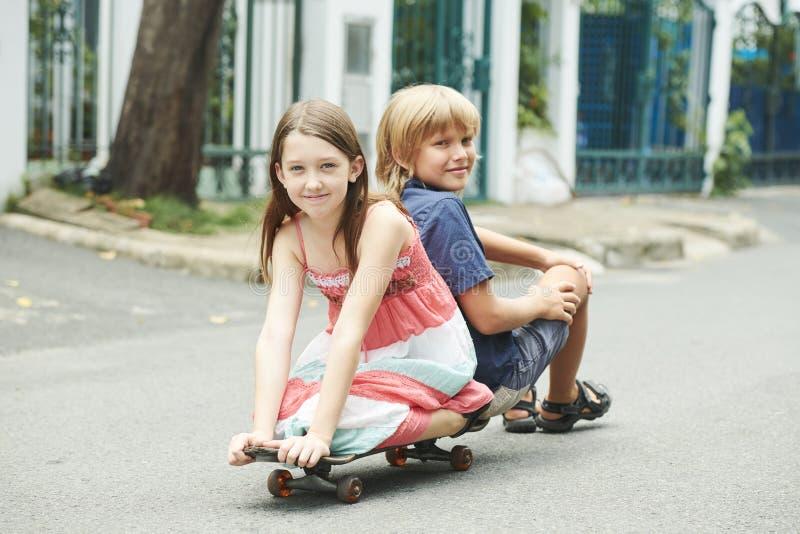 Enfants gais sur la planche à roulettes photographie stock