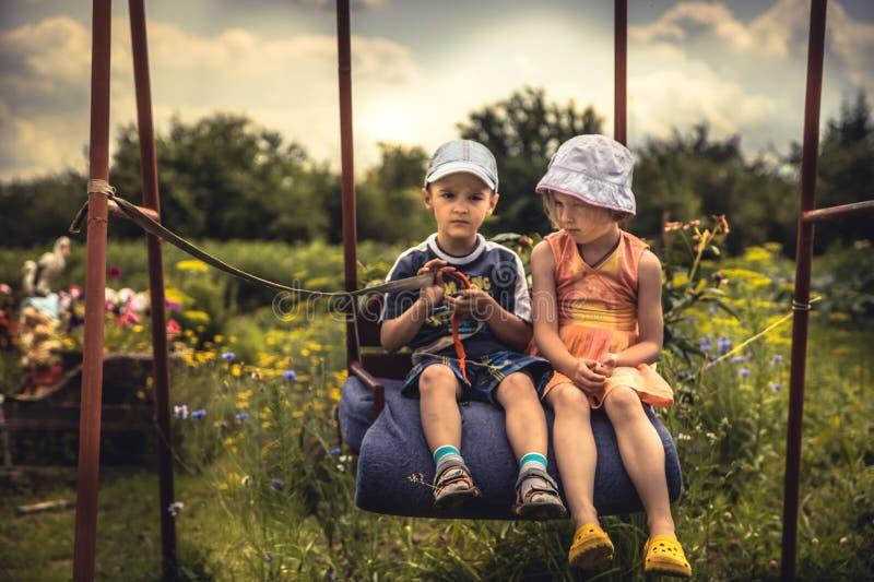 Enfants garçon et fille balançant ensemble dans le jour d'été sur l'arrière-cour dans le chilhood heureux de concept de campagne images stock