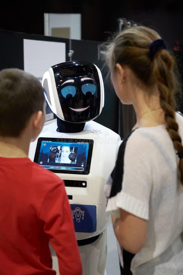 Enfants garçon et parler de fille, jouant avec un robot androïde photos stock