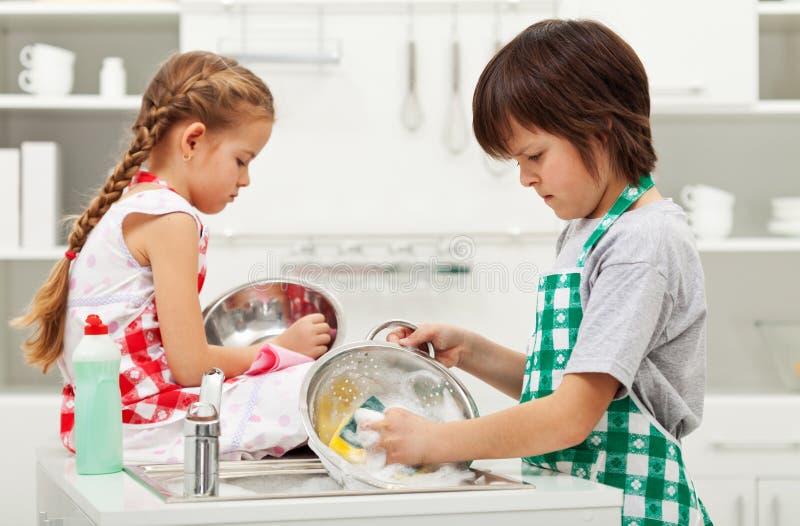 Enfants grincheux faisant les corvées à la maison - plats de lavage photos libres de droits