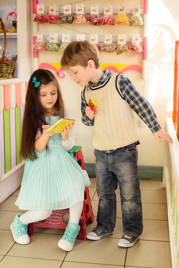Enfants heureux à l'aide de la tablette dans la boutique de sucrerie image libre de droits