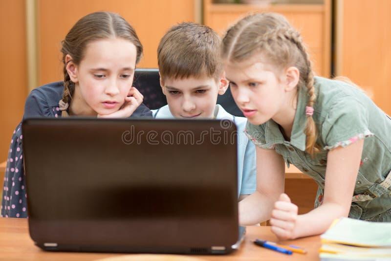 Enfants heureux à l'ordinateur portable dans la salle de classe photos libres de droits
