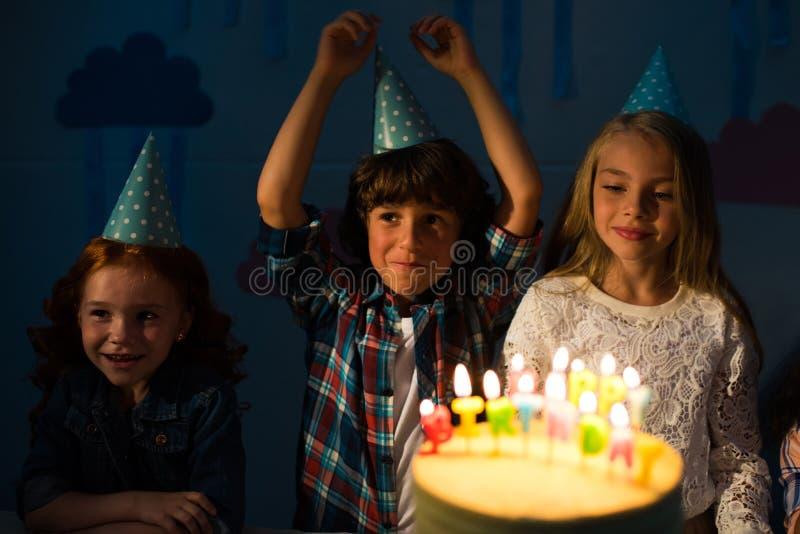 enfants heureux adorables tenant le gâteau d'anniversaire proche avec les bougies brûlantes photos stock
