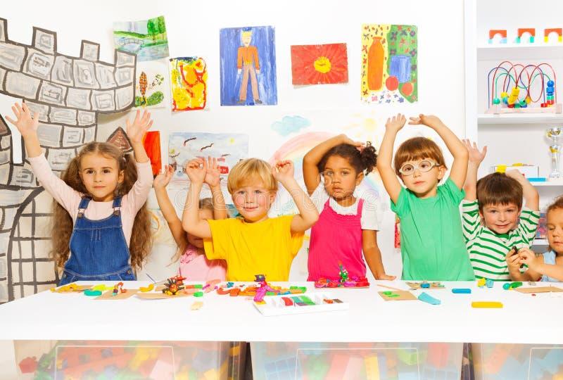Enfants heureux avec de la pâte à modeler dans la classe de jardin d'enfants photo stock