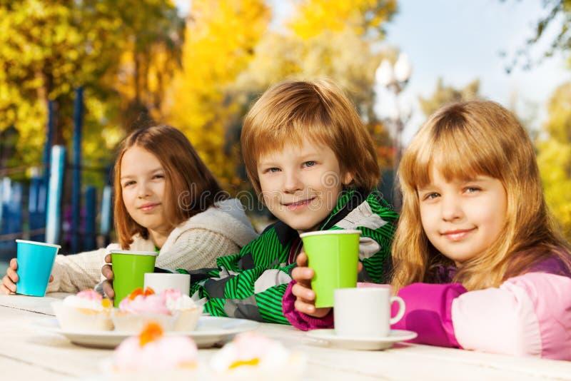 Enfants heureux avec des tasses de thé se reposant dehors image libre de droits