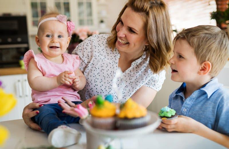 Enfants heureux avec la mère mangeant des petits gâteaux images stock