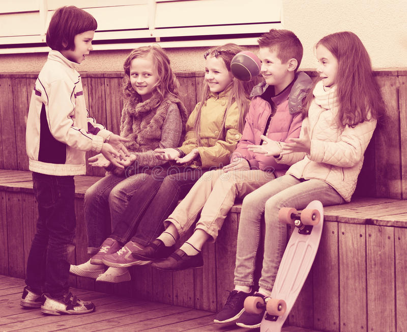 Enfants heureux avec la petite boule jouant dans la rue photo stock