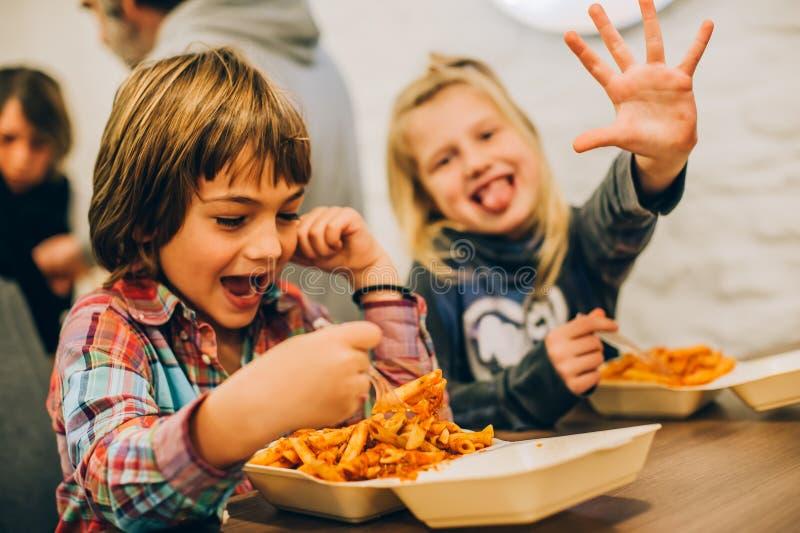 Enfants heureux ayant l'amusement tout en mangeant des pâtes de spaghetti photographie stock