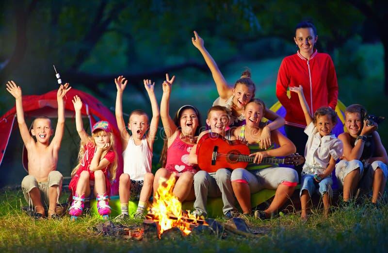 Enfants heureux chantant des chansons autour du feu de camp image stock