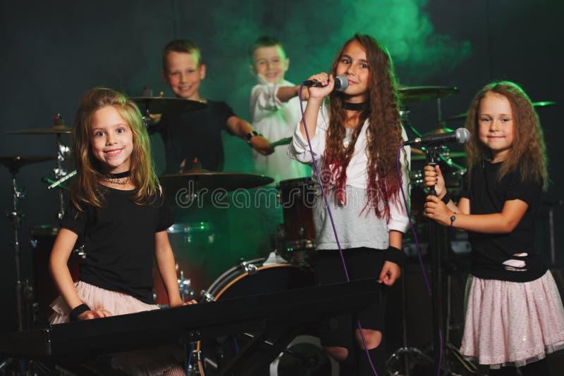 Enfants heureux chantant et jouant la musique photographie stock